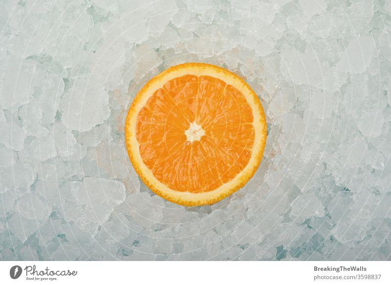 Frische Orangenschnittscheibe über zerstoßenem Eis orange eine Hälfte geschnitten Scheibe frisch zerdrückt Hintergrund Nahaufnahme blau weiß kalt gefroren