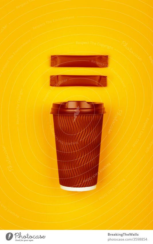 Kaffeetasse aus braunem Papier über gelb Tee Tasse Einwegartikel dunkel eine Verschlussdeckel lebhaft kleben Beutel zwei Zucker Hintergrund Nahaufnahme heiß