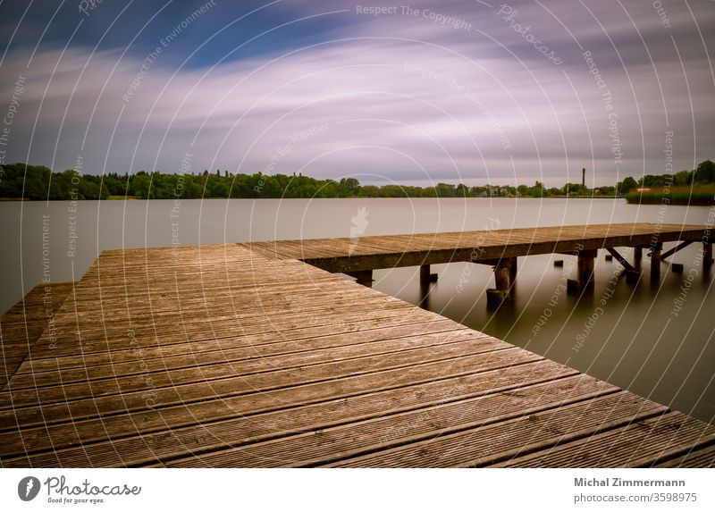 Steg an einem See Seeufer Wasser Wasseroberfläche grün Holz Natur Naturliebe Naturerlebnis Frühling Außenaufnahme Menschenleer Landschaft Farbfoto