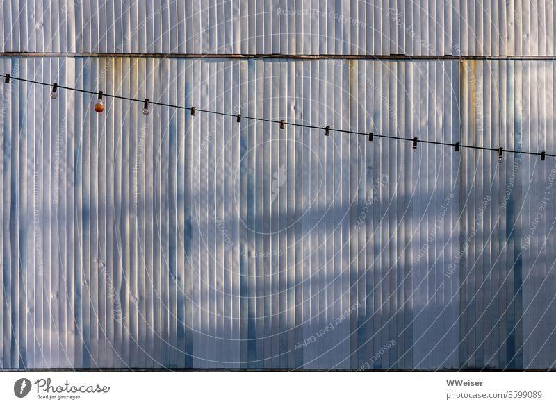 Lichterkette vor der Wellblechwand eines Containers, Abendlicht Glühbirnen Lampen Beleuchtung Schnur Deko Gartenfest Wand Fassade Verläufe verwittert Rost alt