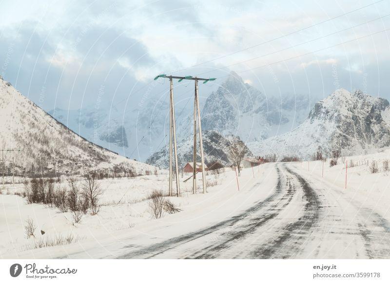 verschneite Straße in Norwegen führt unter einer Stromleitung hindurch vor Bergen mit Schnee Lofoten Skandinavien Winter Strommast Energieversorgung