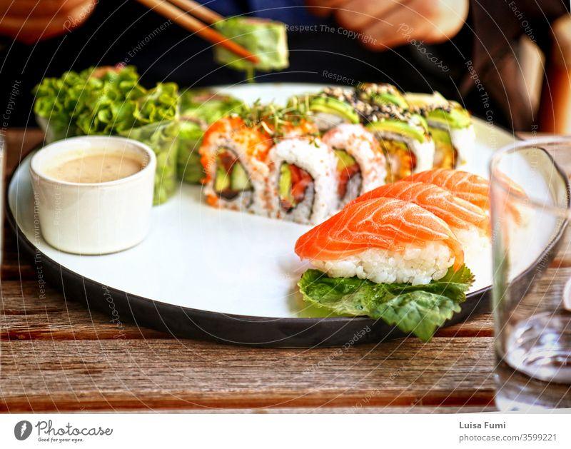 Sushi- und Nigiri-Platte nach japanischer Art im Restaurant Oudoors, Weichzeichner Lebensmittel Japanisch Lachs rollen Teller Salatbeilage asiatisch Reis