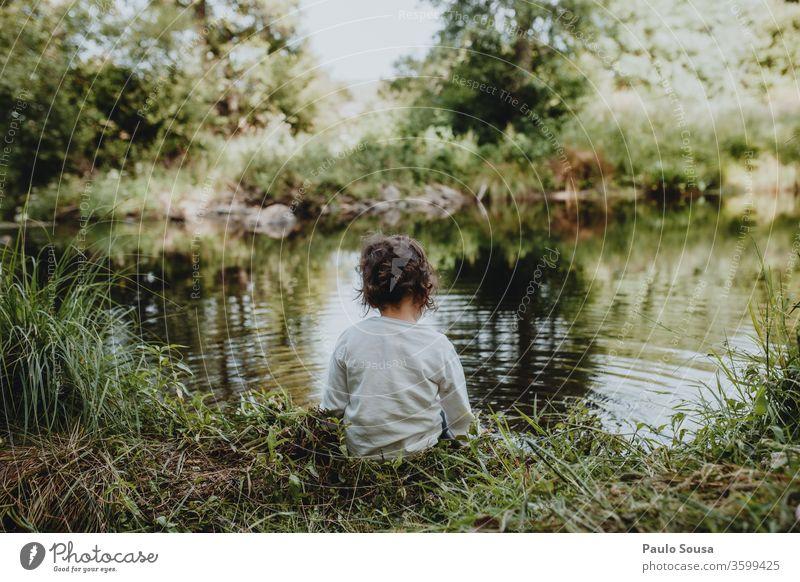 Kleines Mädchen am Fluss sitzend Kind Rückansicht Kaukasier 1-3 Jahre Mensch Farbfoto Kindheit Außenaufnahme 3-8 Jahre Kleinkind Tag Spielen beschaulich Sommer