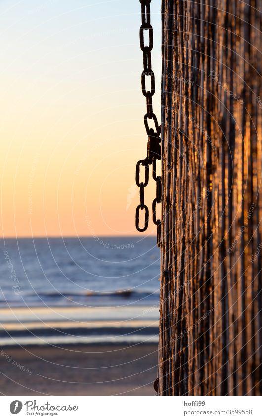 Kette an Holzpfahl am Strand bei Sonnenuntergang Sommerurlaub romantische Stimmung Rost Pfahl Kettenglied Meer Schwache Tiefenschärfe Urlaubsstimmung Erholung