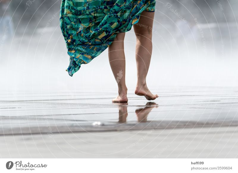 die junge Frau geht Barfuß über eine nasse Fläche - der Sprühnebel des Miroir d'eau sorgt für eine willkommene Abkühlung Fuß Beine Zehen Haut Wasser Schatten