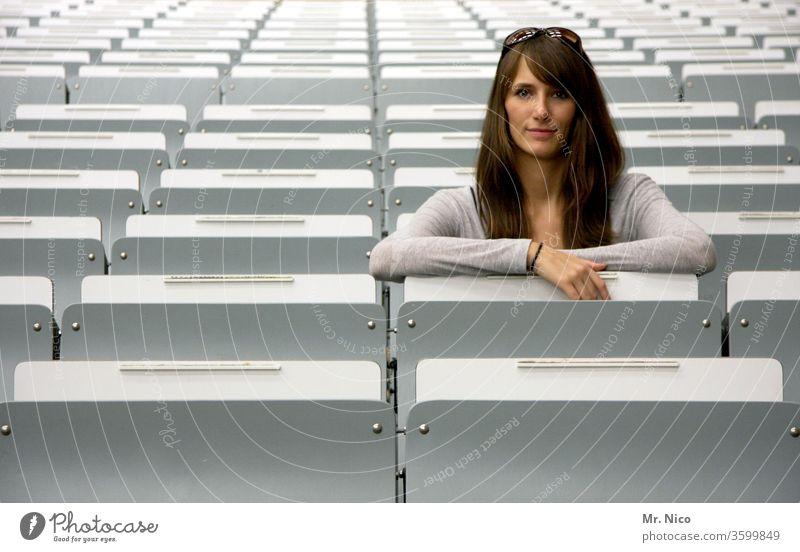 junge Frau sitzt in der zweiten Reihe zuschauerplätze Publikum Veranstaltung Sitzgelegenheit Platz leer Tribüne Sitzreihe nebeneinander Strukturen & Formen