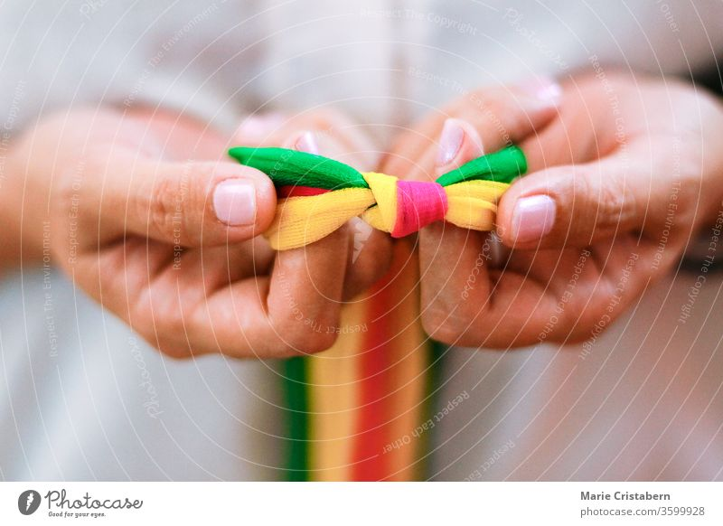Hände halten regenbogenfarbene Bänder zur Feier des Tags des Stolzes, der Zerstreuung, der Gleichberechtigung und der LGBTQ-Gemeinschaft Tag des Stolzes