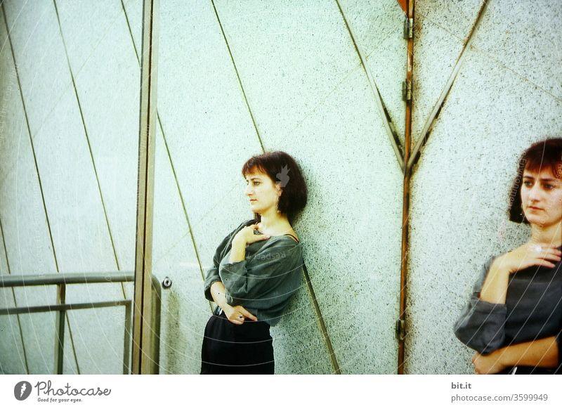 Junge nachdenkliche Frau steht an der Wand, neben ihrem Spiegelbild, in der Stadt. Hübsche, schlanke, schöne Frau im Doppelpack, angelehnt an Fassade im Blauton. Gespiegelte traurige, skeptische, ernste, besorgte Person denkt ängstlich an ihre Zukunft.