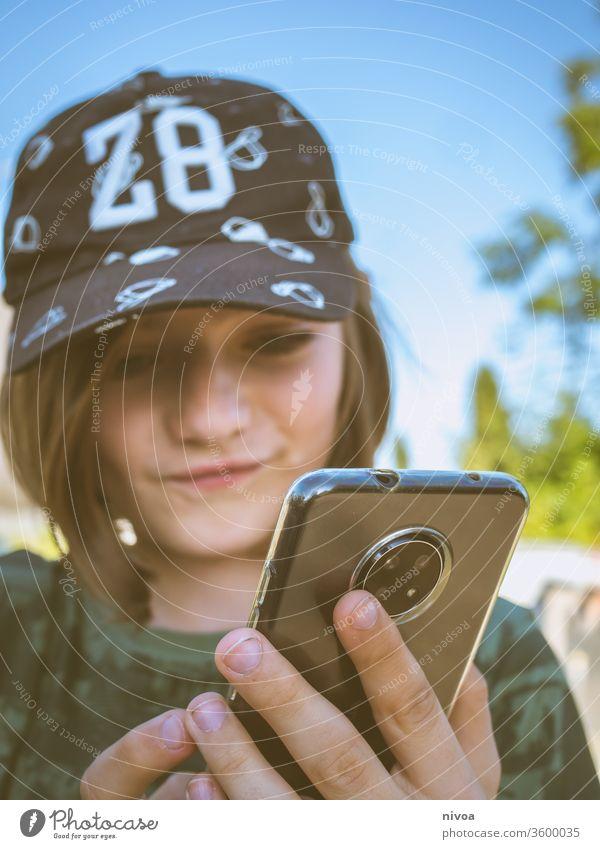 Junge mit Smartphone Verschlussdeckel Kindheit Fotokamera Sommer Blick in die Kamera Kindheitserinnerung Mensch Porträt Farbfoto Freude Tag Gesicht
