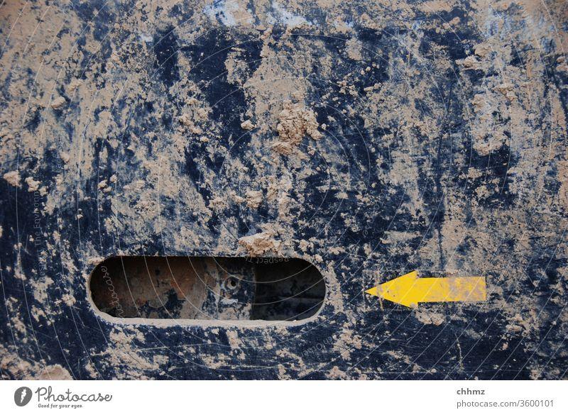 Gelber Pfeil gelb links dreckig Dreck Metall Stahl schwarz Bagger Loch Textfreiraum oben Baustelle Schlamm schlammig Maschine Menschenleer hinweisen