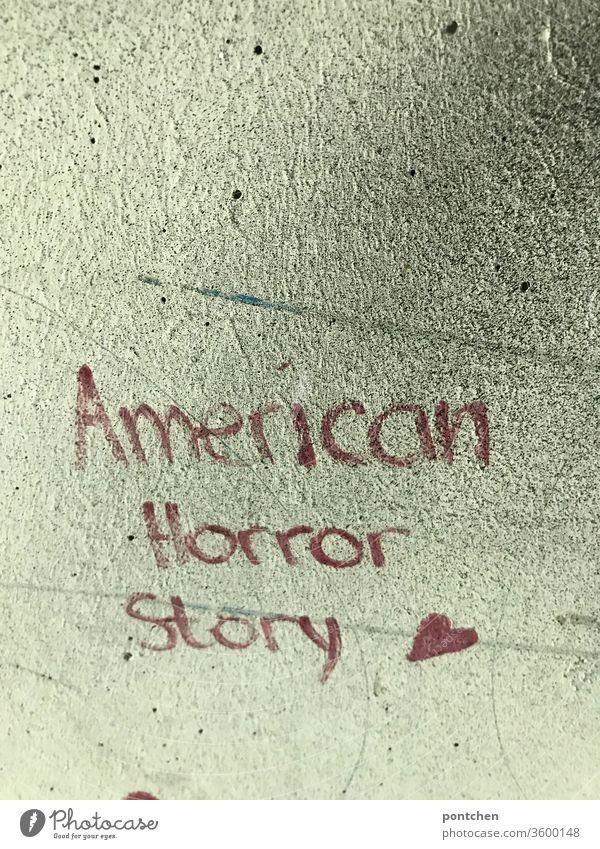 American Horror Story steht mit roter Schrift auf einer Hauswand. Politik, USA, krise. Filmtitel. Trump American Horror story politik trump weltgeschehen