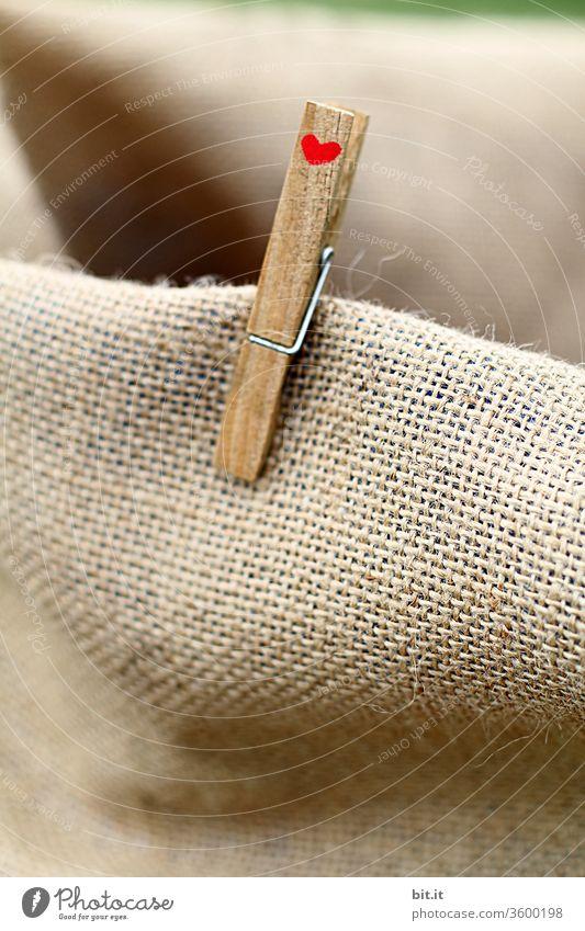 Alte, braune Wäscheklammer aus Holz mit kleinem, rotem Herz klammert an einem Stoffstück aus Jute. Symbol für Nachhaltigkeit durch abbaubare Verpackungen und EInkaufen mit Taschen aus natürlichem Material. Zeichen für Liebe, Freundschaft und Zusammenhalt.