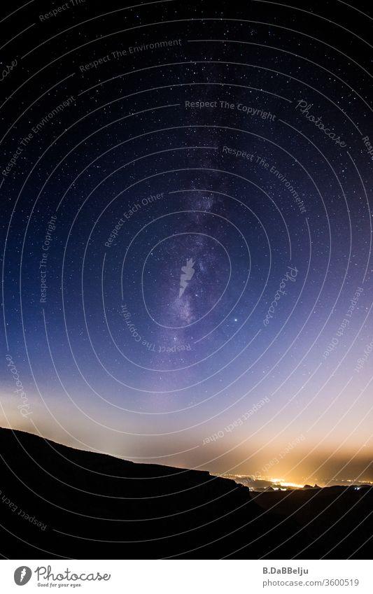 Die Milchstraße vom Jabal Akhdar, dem höchsten Punkt des Omans (ca. 3000 m). In der Ferne leuchtet die nächste Stadt in der Dunkelheit. Berge Reisen