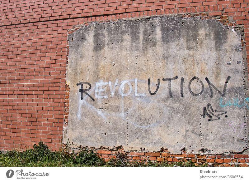 Graffiti Schriftzug REVOLUTION auf Wandputz an einer roten Backsteinwand Schriftzug Revolution Schriftzeichen Mauer Fassade Gebäude Textfreiraum links