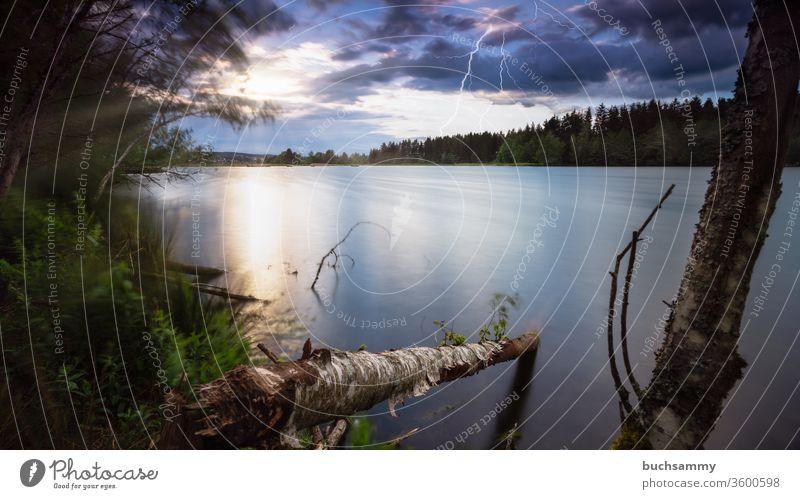 Sonnenuntergang an einem See mit gleichzeitig aufziehendem Gewitter und Blitzen. Landschaft sehen Gewässer Himmel dramatisch wolken feuchter blitze Unwetter