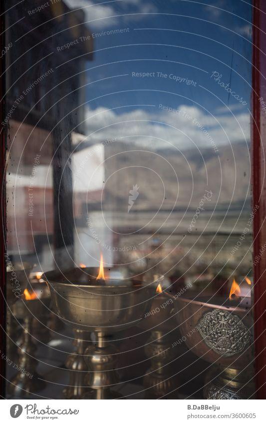 Antike tibetische Öllampen hinter einer Fensterscheibe, in der sich ein Gebirgszug des Himalayas spiegelt. Felsen Natur Gebirge Berge Tal hoch Farbfoto Himmel