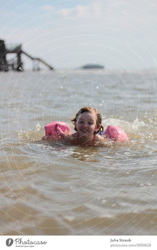 Kleinkind mit Schwimmflügl badet in der Nordsee baden kalt frisch Schwimmen & Baden schwimmflügl Tropfen Wassertropfen Meer Steg Mädchen spaßig Spaß haben
