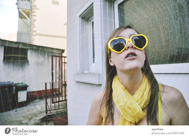 jugendliche mit gelber herzsonnenbrille und gelbem schal in gelbem bikini steht in einem etwas heruntergekommenen hinterhof und schaut nach oben Mädchen
