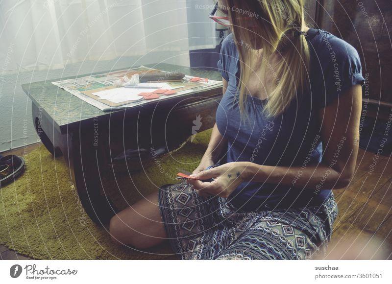 frau sitzt auf dem boden und schneidet etwas aus Frau Zuhause zeichnen basteln ausschneiden Schere Papier Tisch Fußboden Haare & Frisuren Brille Oberkörper