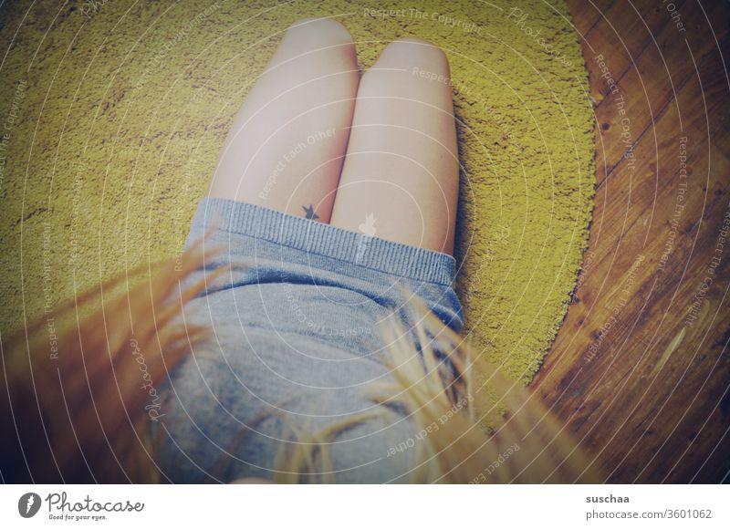 auf dem boden sitzend auf die eigenen beine gucken | symmetrie Frau weiblich Beine feminin Teppich auf dem Fußboden Haare Holzboden Tattoo Stern Symmetrie