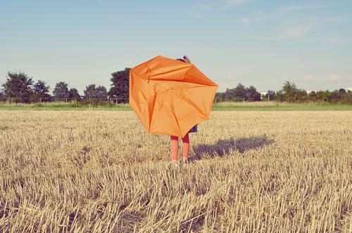 kind auf einem strohacker mit kaputtem regenschirm Kind Regenschirm orange Acker Feld Strohfeld Getreidefeld Landwirtschaft Landschaft Ackerwirtschaft Sommer