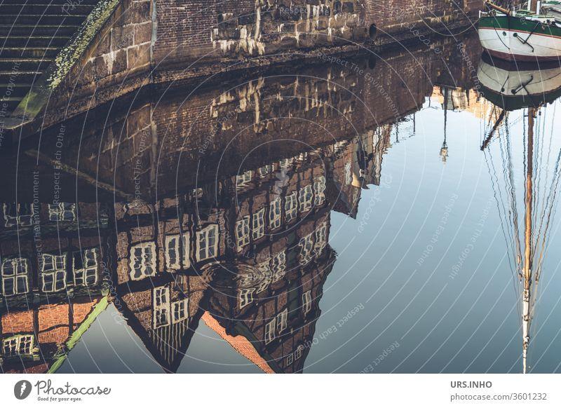 Im Wasser spiegeln sich die alten Fachwerkhäuser  und der Mast vom Segelschiff Altstadt Spiegelung Reflexion & Spiegelung Stadt Tag Kaimauer Ewer