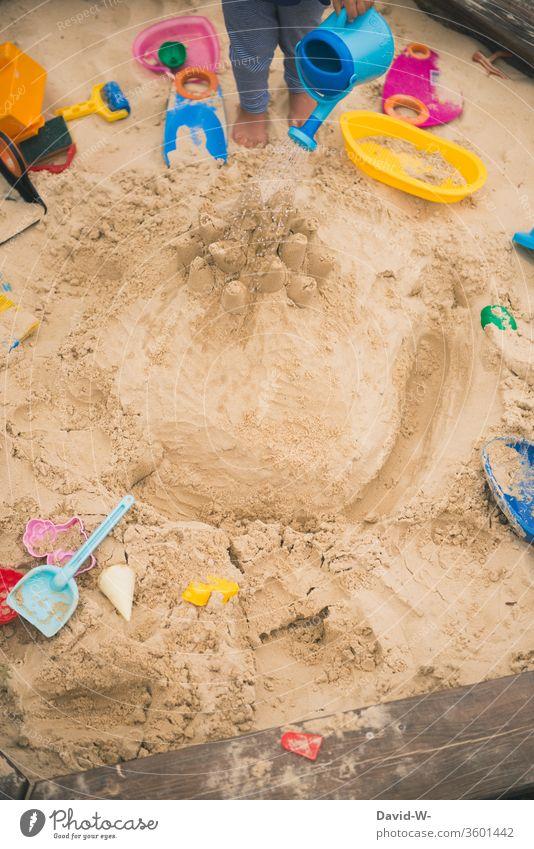 Kind spielt im Sandkasten Spielzeug Spaß Freude selbstbeschäftigung anonym gießen Wasser nass Gießkanne sandig garten Spielplatz Spielen Außenaufnahme Kleinkind