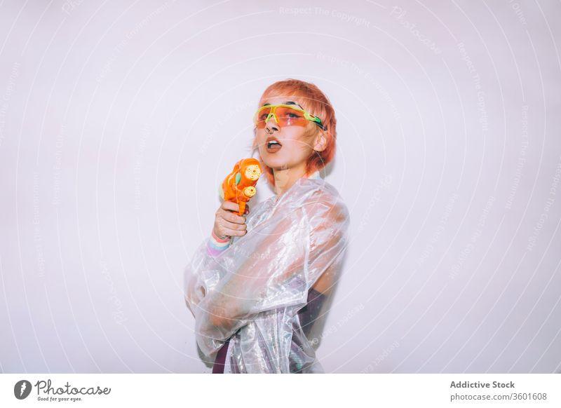 Retro-futuristische Frau, die eine Waffe auf die Kamera richtet Pistole zielen angriffslustig Stil jung Outfit retro Model Wasser Punkt gefärbtes Haar trendy