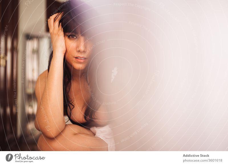 Sinnliche Frau in Dessous in moderner Wohnung Unterwäsche sinnlich Körper Gelassenheit Windstille Figur Anmut verführerisch Zeitgenosse Appartement sitzen