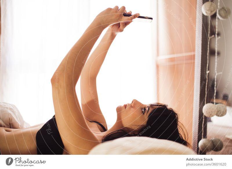 Zufriedene Frau mit Smartphone im Bett Browsen sich[Akk] entspannen benutzend Lügen Schlafzimmer Dessous Wochenende Apparatur Gerät ruhen Decke Mobile Telefon