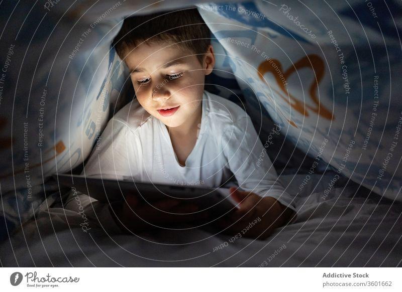 Entzückter Junge sieht Zeichentrickfilm auf dem Tablett Kind benutzend Tablette Decke Nacht zuschauend heiter Karikatur Pyjama heimwärts bezaubernd Gerät