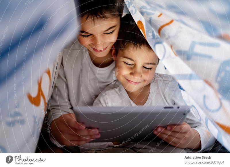 Glückliche Brüder sehen sich gemeinsam ein Video auf einem Tablet an zuschauen Karikatur Zusammensein Tablette Bruder Geschwisterkind Pyjama Decke benutzend