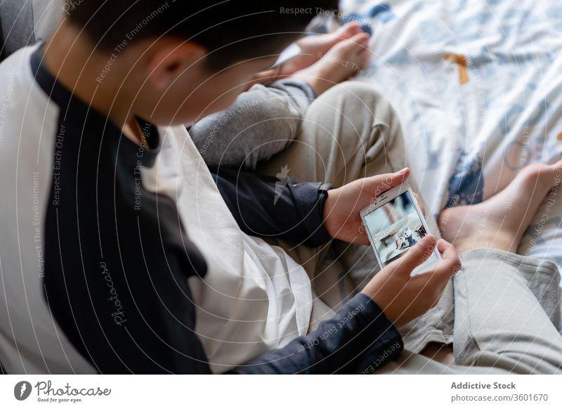 Geschwisterkulturen mit Smartphone am Bett Geschwisterkind benutzend zuschauen Karikatur sich[Akk] entspannen heimwärts Kinder Bruder gemütlich Kindheit Gerät