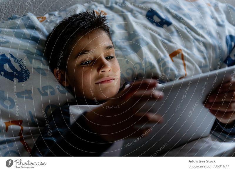 Entzückter Junge benutzt Tablette am Wochenende im Schlafzimmer Kind benutzend Decke Nacht zuschauend heiter Pyjama heimwärts bezaubernd Gerät Apparatur