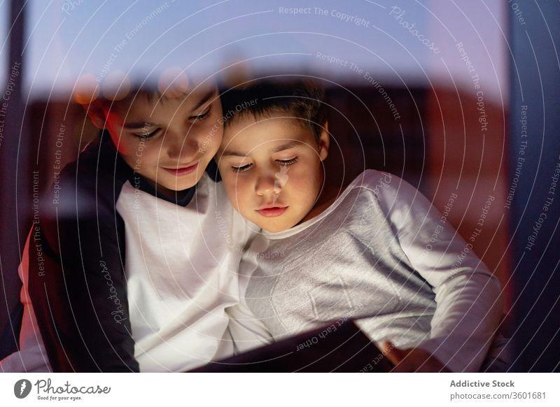 Süße Brüder schauen gemeinsam Zeichentrickfilm auf dem Tablett zuschauen Video Tablette Wochenende Kind Karikatur Bruder Zusammensein kuscheln benutzend Junge