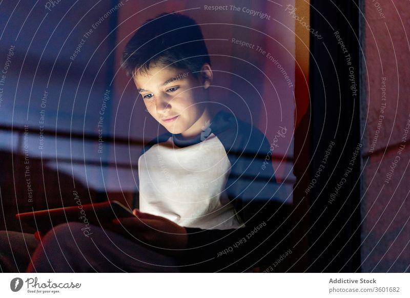 Browsing-Tablette für Kinder am Abend benutzend Browsen Gerät Wochenende unterhalten spielen online dunkel lässig Apparatur heimwärts Anschluss Appartement