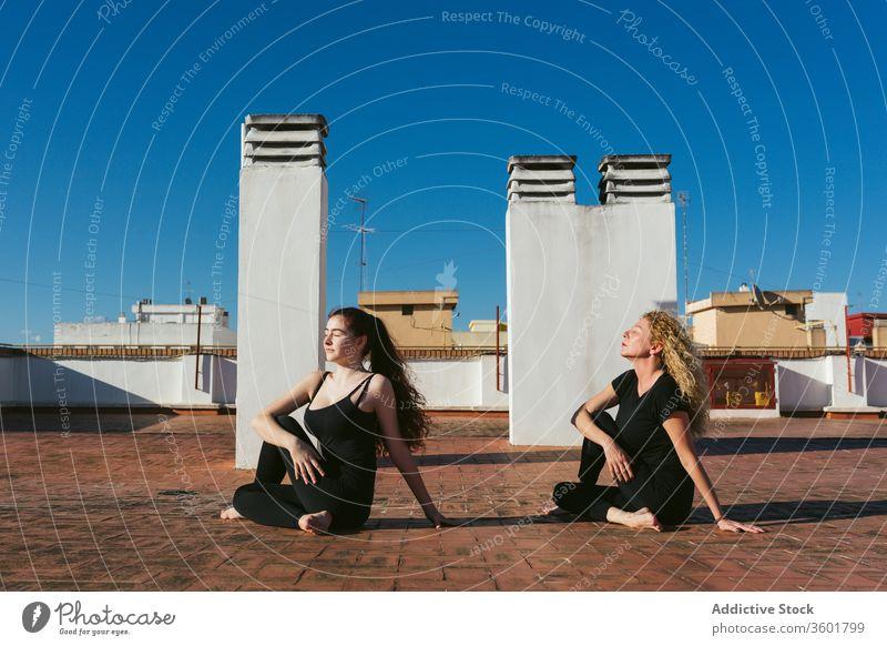 Frauen praktizieren gemeinsam Yoga auf dem Dach Zusammensein Dachterrasse Terrasse üben Pose positionieren ardha matsyendrasana verdrehen Halbherr der Fische