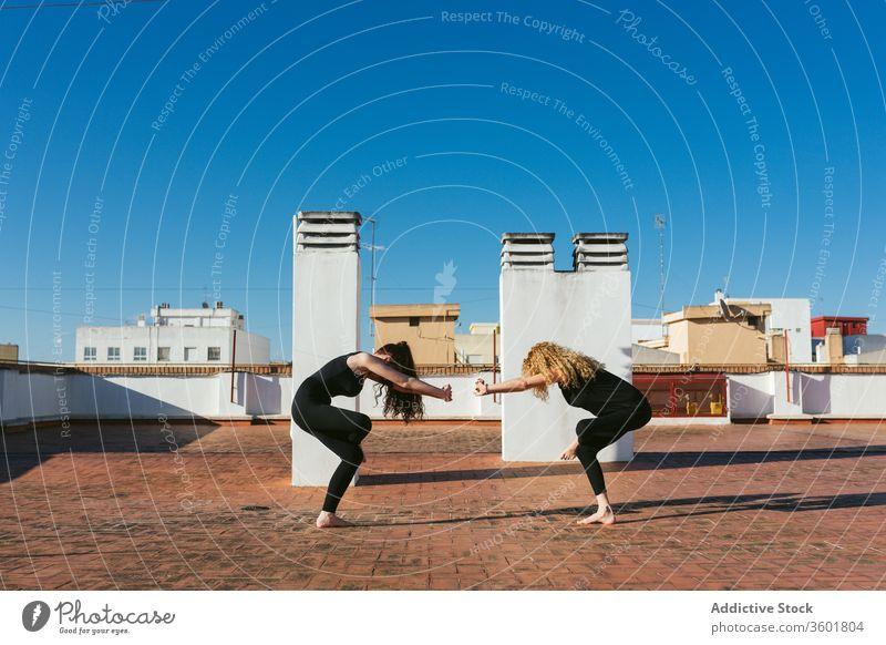 Frauen praktizieren gemeinsam Yoga auf dem Dach Zusammensein Dachterrasse Terrasse üben Pose positionieren verdrehen Akro-Yoga Mutter Tochter Lifestyle Harmonie