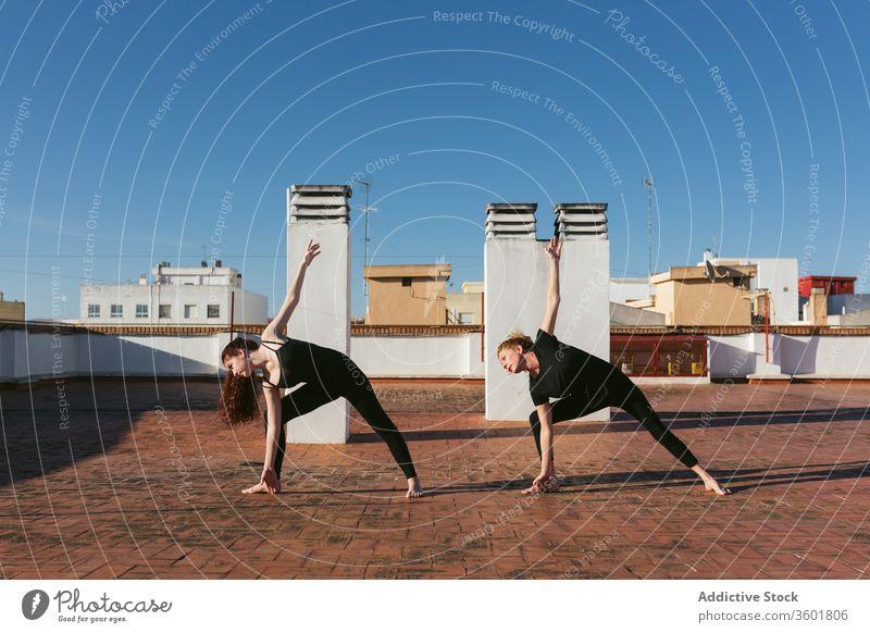 Frauen, die Twist-Yoga praktizieren, posieren auf dem Dach Zusammensein üben gedrehtes Dreieck parivrtta trikonasana Pose verdrehen stehen Dachterrasse
