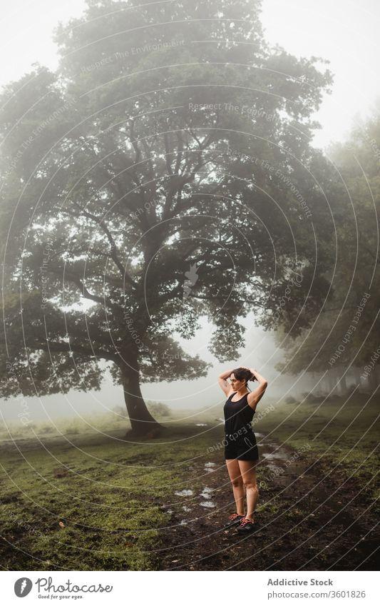 Fitnesssportlerin wärmt sich beim Training im Wald auf Aufwärmen Sportlerin Übung Wälder Morgen Nebel Sportkleidung dreckig Weg Gesundheit Ausdauer Athlet