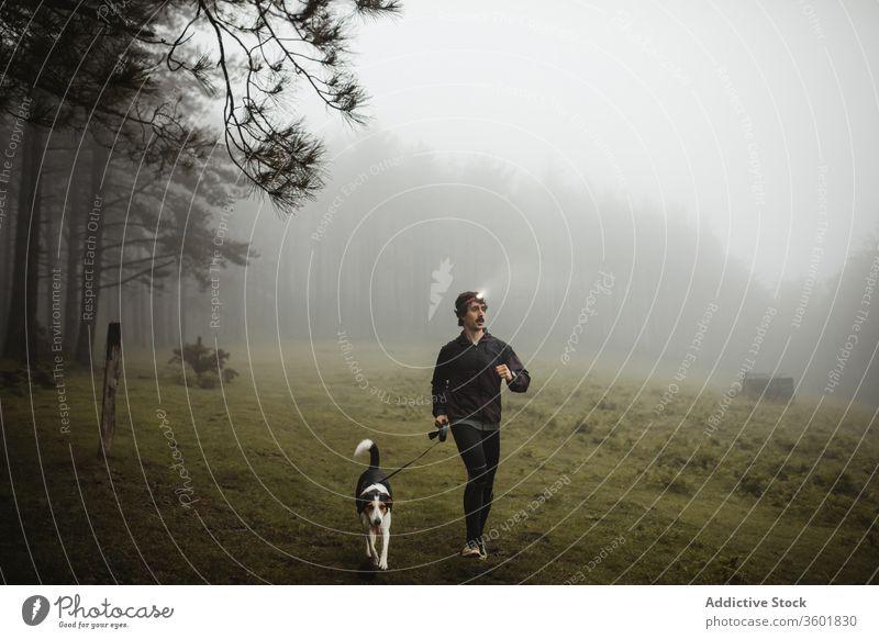 Fitnesssportler rennt mit Hund in nebligem Wald Läufer Sportler laufen Training joggen Jogger Nebel Holz männlich Sportbekleidung selbstbewusst Gesundheit