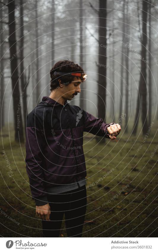 Männlicher Läufer überprüft Armbanduhr während des Trainings prüfen Sportler passen Sportkleidung Wald Nebel Morgen männlich Fackel Taschenlampe Athlet