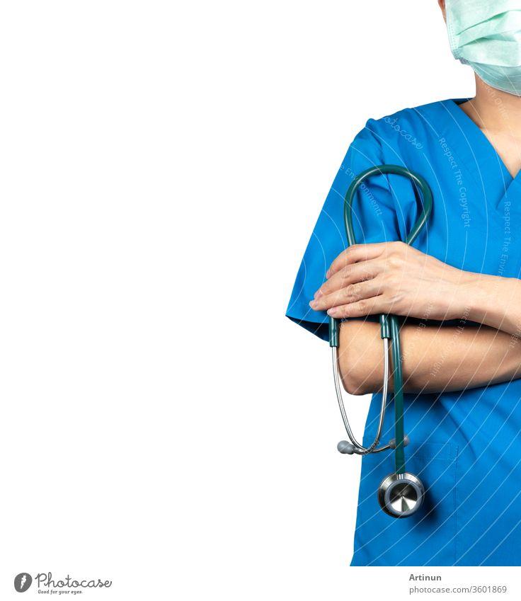 Chirurgen tragen blaue OP-Hemduniform und grüne Gesichtsmaske. Arzt steht mit verschränkten Armen und hält das Stethoskop in der Hand. Arzt im Gesundheitswesen. Chirurg steht mit Zuversicht. Vertrauen.