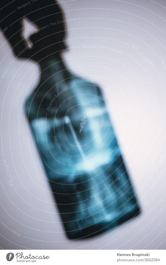 Griff zur Flasche Gin blau Lichtspiel Schatten Hand festhalten Glas Getränk Alkohol trinken