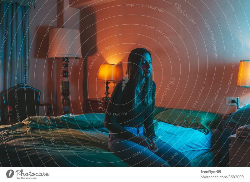 Junge Frau sitzt traurig auf dem Bett Porträt Nacht Quarantäne Depression Kopfkissen Coronavirus covid-19 Isolation selbstisoliert spät Schlafstörung blau