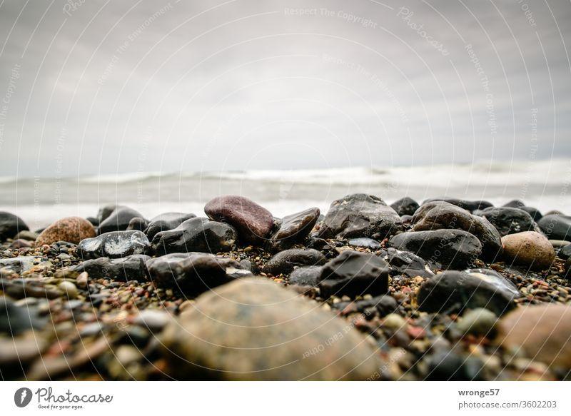 Nasse glänzende Steine liegen am Strand vor den sich hoch auftürmenden Wellen der Ostsee Steinstrand nass Ostseestrand hohe Wellen auftürmende See Brandung Meer