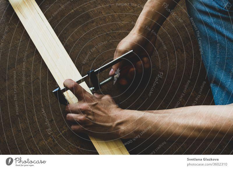 Männerhände befestigen die Klemme an den Holzschienen und nehmen vor dem Schneiden eine Messung vor. Reparatur-Konzept Werkzeug heimwärts Arbeit Konstruktion