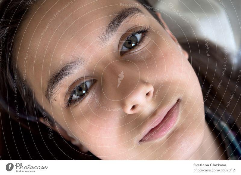Porträt eines schönen, jungen, kaukasisch gebräunten Mädchens auf weißem Hintergrund in Nahaufnahme. Lange Wimpern und natürlich braune Augenbrauen, grünes Auge, Schönheitskonzept