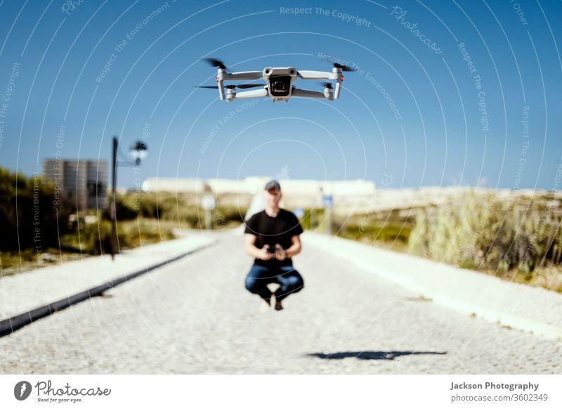 Mann, der zusammen mit seiner Drohne das Fernfliegen festhält Dröhnen Fliege Flug Hubschrauber Technik & Technologie Konzept aladin Fröhlichkeit sonnig Straße