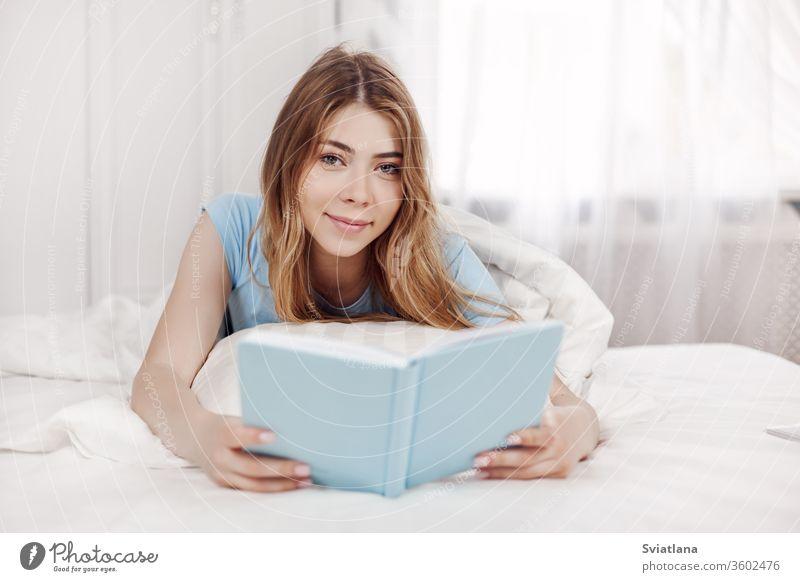 Hübsches Mädchen im blauen Pyjama, ein Buch lesend, auf dem Bett im Schlafzimmer liegend. Ausbildung, Erziehung, Hobbys. Raum lautet Lügen heimwärts Freizeit